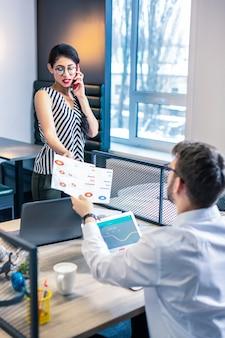 Все под контролем. серьезный молодой менеджер разговаривает по телефону, находясь в офисе