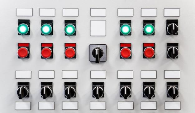 Панель управления промышленным оборудованием с заводскими табличками, переключателями, красными кнопками и светящимися зелеными кнопками