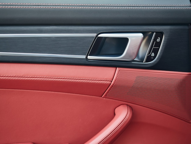 Control panel with chrome handle on the car door red genuine leather in a new car with arm rest with...