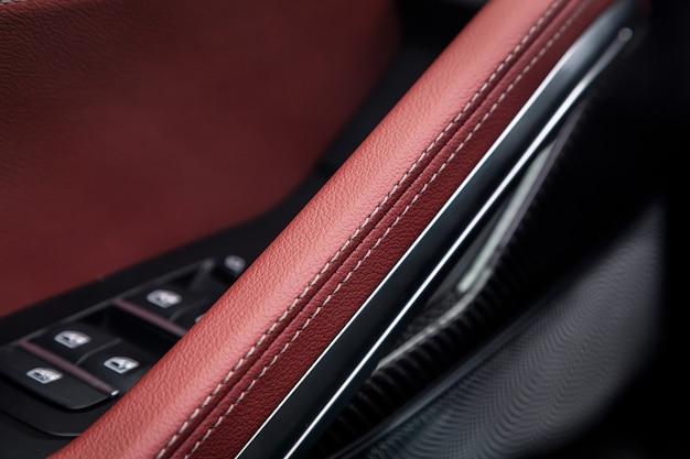 Панель управления с хромированной ручкой на двери автомобиля, обычная черная и красная натуральная кожа в новой машине. подлокотник в роскошном автомобиле