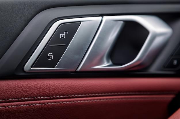 車のドアにクロームハンドルが付いたコントロールパネル、新車の一般的な黒と赤の本革。コントロールボタン付きアームレスト