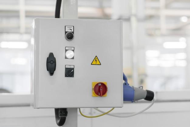 Блок управления какой-либо производственной линией или станком на размытом фоне интерьера цеха