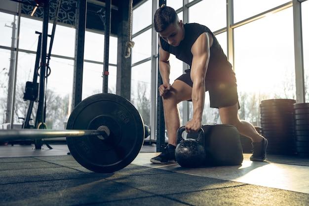 コントロール。若い筋肉質の白人アスリートがジムでトレーニングし、筋力トレーニングを行い、練習し、ウェイトとボールを使って上半身に働きかけます。フィットネス、ウェルネス、スポーツ、健康的なライフスタイルのコンセプト。