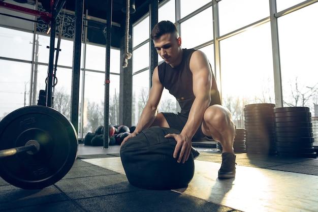 제어. 젊은 근육질의 백인 운동선수는 체육관에서 훈련하고, 근력 운동을 하고, 연습하고, 웨이트와 공으로 상체를 운동합니다. 피트니스, 웰빙, 스포츠, 건강한 라이프 스타일 개념.