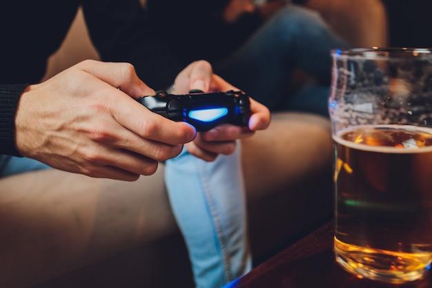 손에 컨트롤러 또는 비디오 게임 조이스틱 콘솔. 게임 개념을 닫습니다.