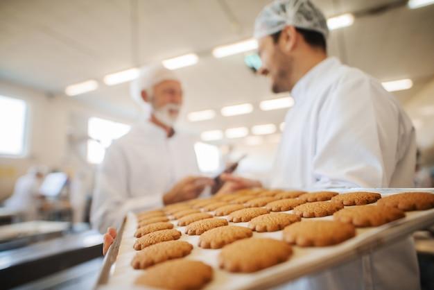 タブレットを使用しているときにワーカーと話しているコントローラー。クッキーとプレートを運ぶ労働者。防護服。食品工場のインテリア。クッキーに重点を置いています。