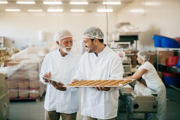 タブレットを使用しているときにワーカーと話しているコントローラー。クッキーとプレートを運ぶ労働者。防護服。食品工場のインテリア。