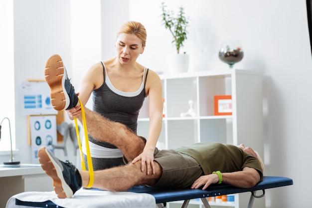 すべてを制御します。運動のパフォーマンスを制御しながら彼女の患者の脚を見ている美しいブロンドの女性