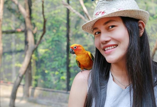太陽のconureオウムと美しいアジアの女性。