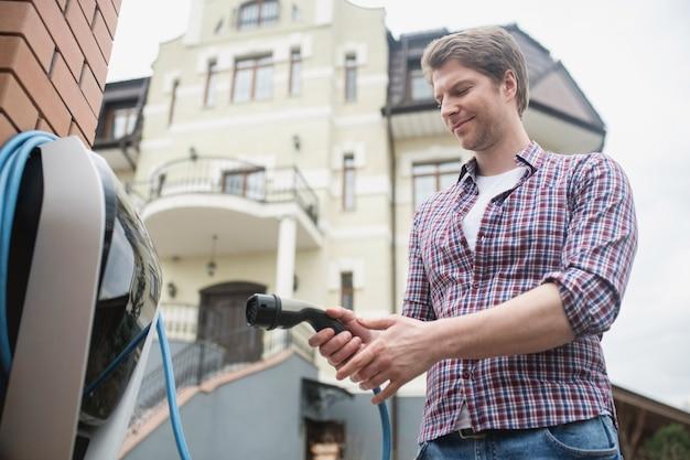 Удобство. довольный мужчина в клетчатой рубашке стоит на улице на территории дома возле зарядной станции для электромобиля