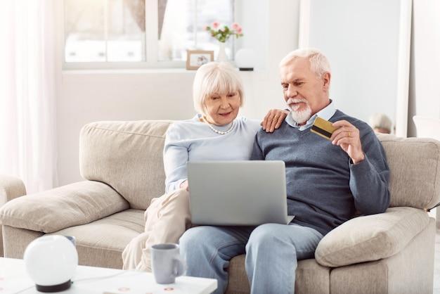 Удобное обслуживание. жизнерадостная пожилая пара сидит на диване и оплачивает коммунальные услуги онлайн с помощью банковской карты
