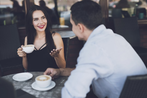 Conversation of girl with man in cafe for coffee mug.