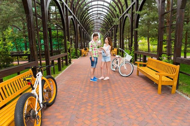 아름다운 공원의 아치 밑에서 자전거를 타고 녹색과 빨간색 체크무늬 셔츠를 입은 소녀와 남자의 대화