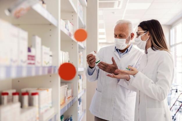 약에 대한 두 약사의 대화. 젊은 여성과 노인은 약국에서 의료인으로 일하고 약 치료에 대해 논의합니다. 그들은 바이러스로부터 보호하기 위해 흰색 유니폼과 마스크를 착용합니다.
