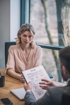 会話。真面目な若いブロンドのビジネスの女性と男性がオフィスに座って協力を議論する論文とスーツを着て