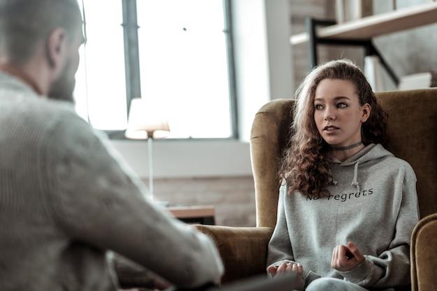심리학자와의 대화. 심리학자와의 대화에 참여하는 느낌을 호소하는 십대 소녀