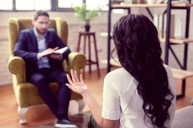 セラピストとの会話。セッションをしながら彼女の医者に話している素敵な若い女性の選択的な焦点