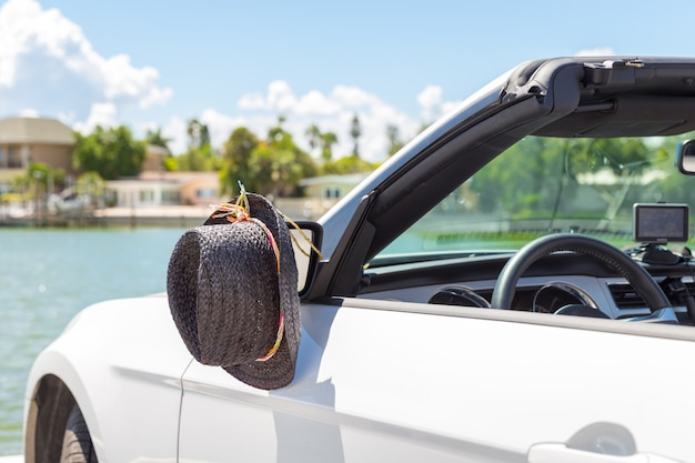 Convertible car with hat hanging on a mirror