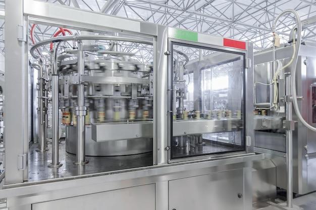 Конвейерная лента в движении при производстве и розливе напитков в жестяные банки