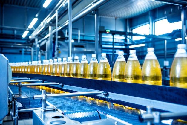 Конвейерная лента с бутылками для сока или воды на современном заводе по производству напитков