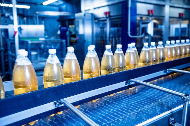 現代の飲料工場のジュースまたは水用のボトルが付いたコンベヤーベルト