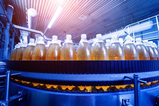 현대적인 음료 공장에서 주스 또는 물을 위한 병이 있는 컨베이어 벨트