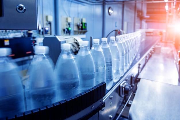 Конвейерная лента с бутылками питьевой воды на современном заводе по производству напитков