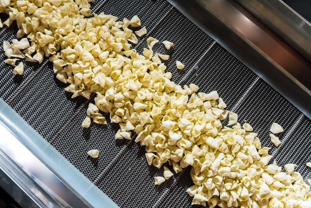 現代の工場でスナックやチップスを揚げるためのコンベアライン