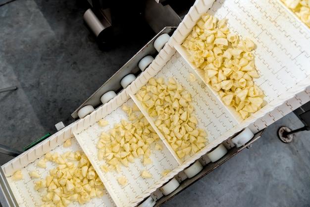 현대적인 공장에서 스낵과 칩을 포장하기위한 컨베이어 라인