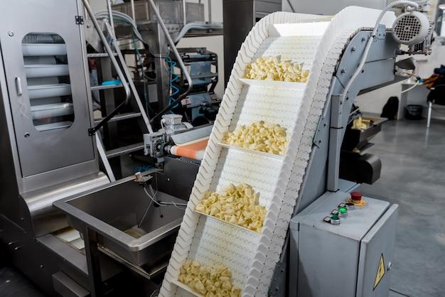 現代の工場でスナックやチップを梱包するためのコンベアライン