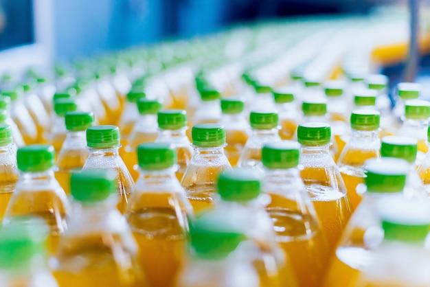 ジュースまたは水のボトルが付いているコンベヤー。飲料工場設備