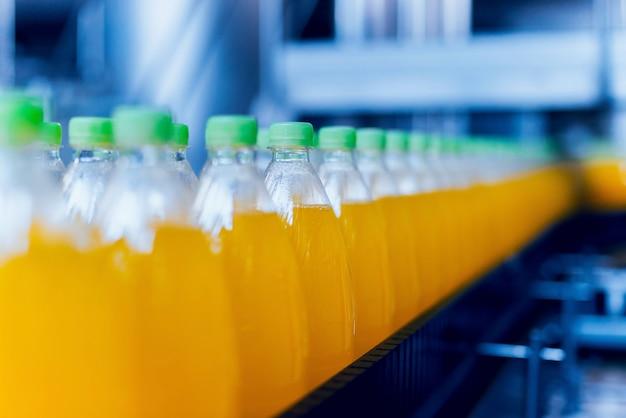 ジュースや水のボトルが付いているコンベヤー。飲料工場設備