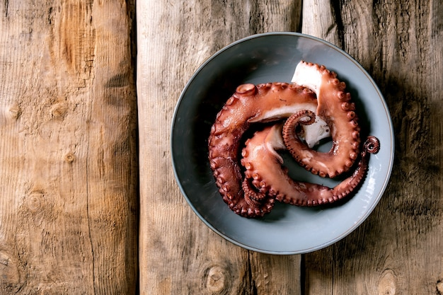 Coocked tentacles of octopus on blue ceramic plate over brown wooden surface. top view, flat lay. copy space