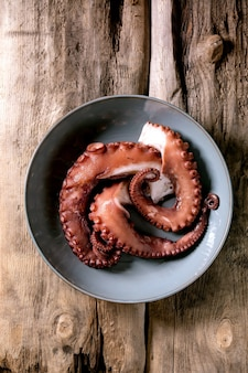 Coocked tentacles of octopus on blue ceramic plate over brown wooden surface. top view, flat lay
