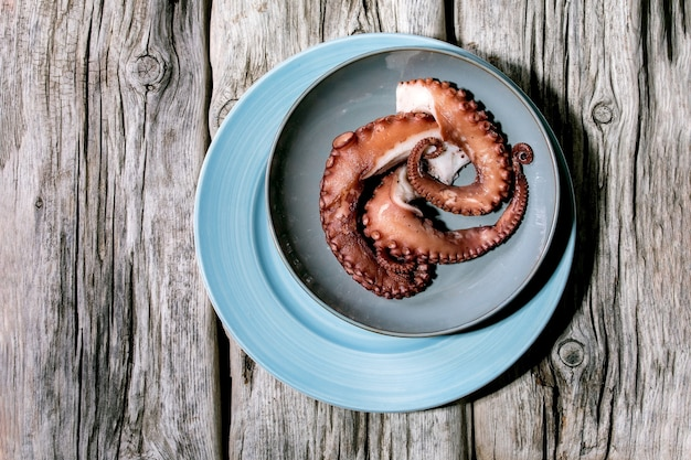 Coocked tentacles of octopus on blue ceramic plate over old grey wooden surface. top view, flat lay. copy space