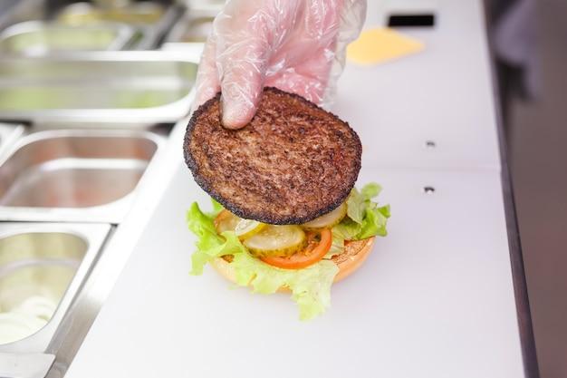 ハンバーガーに肉のカツレツを加えて調理する。レストランでハンバーガーを準備しています。衛生要件に基づいた使い捨て手袋をした調理人の手。