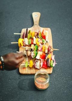 Cook adding seasoning to vegan barbecue skewers