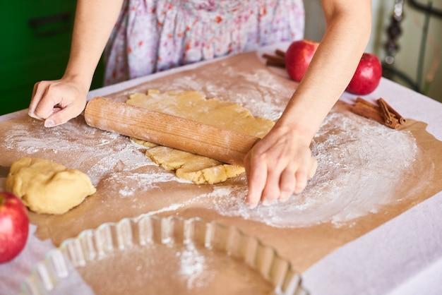 Готовить дома. женщина замешивать тесто для яблочного пирога на кухонном столе. деревенский стиль