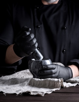 Cook in black latex gloves holding a stone mortar with pepper