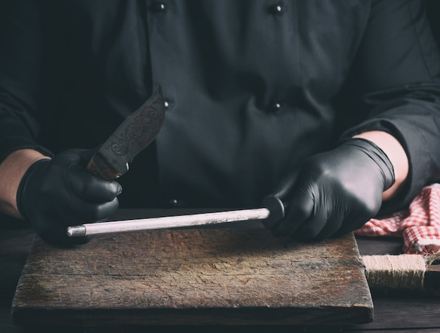 Cook in black latex gloves sharpens a knife over a wooden table