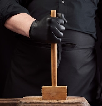 Cook in black uniform holds a wooden hammer for beating meat on a vintage cutting board