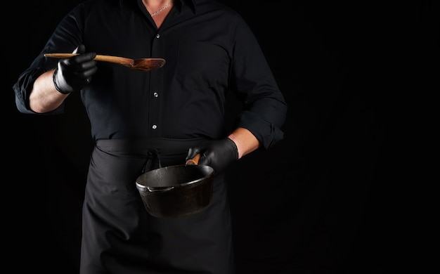 Cook in black uniform and latex gloves holds an empty round vintage black cast iron pan and wooden spoon in front of him, low key, copy space