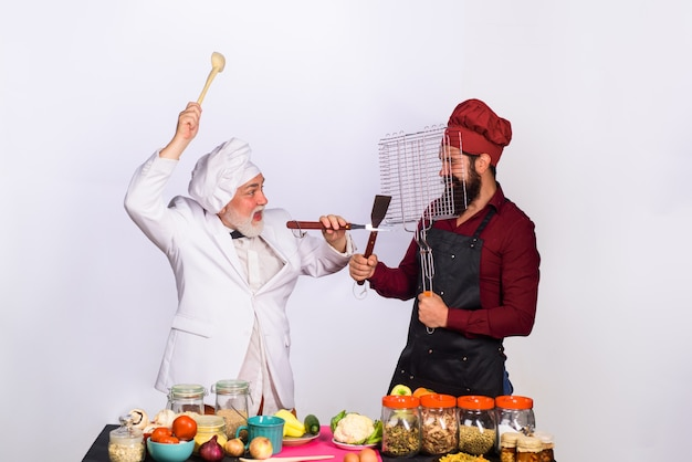 Cook chef two chefs fighting on kitchen professional culinary bearded man in kitchen apron bearded