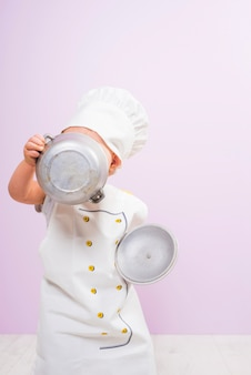 Cook child covering face with pot