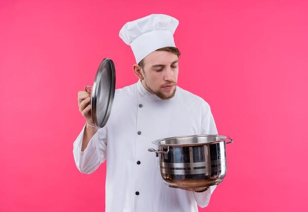 ピンクの壁の上に立っている手に鍋で何かのにおいがする目を閉じて調理する