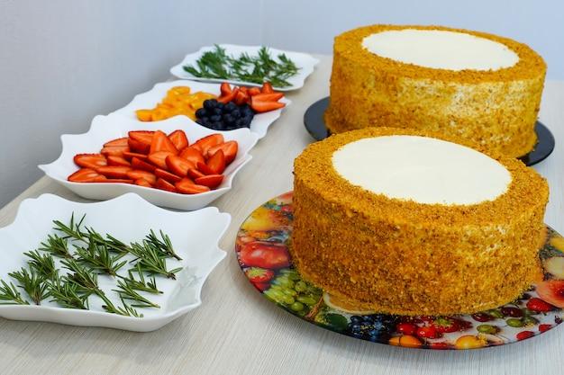 쿡-제과. 기념일을위한 축제 다층 케이크 요리 및 장식. 케이크 장식 준비가되었습니다.