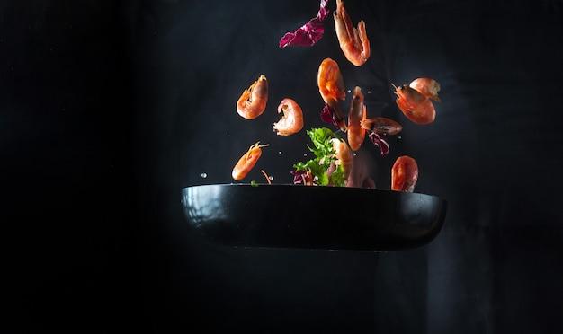 요리사는 야채와 함께 냄비에 새우를 요리합니다. 검은 배경에 해산물, 건강한 채식 음식, 음식을 요리하세요. 움직임이 멈춥니다. 무료 광고 공간