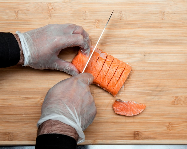 Cook cuts salmon into a slices