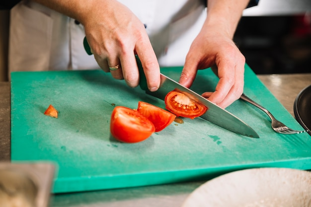 Cook cutting red tomato on board
