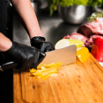 Cook cutting yellow pepper on board